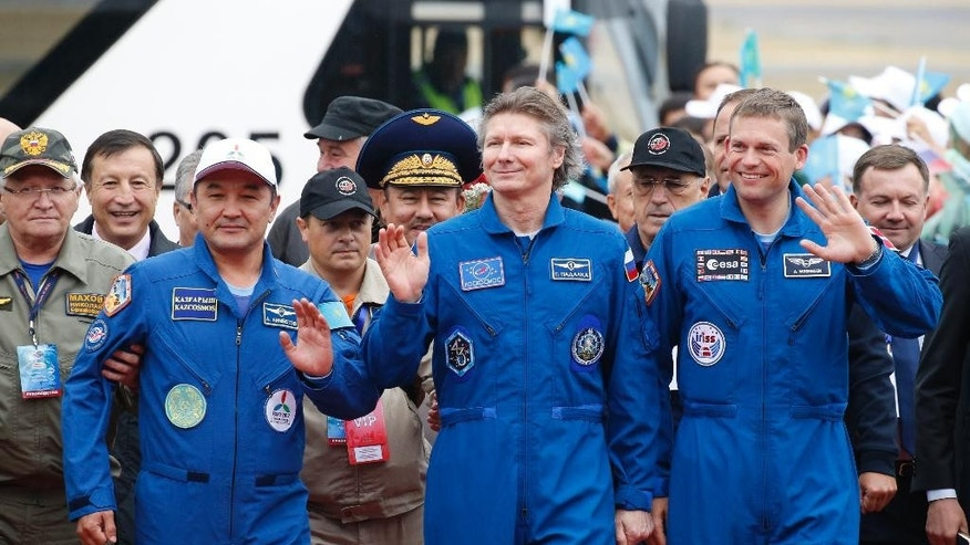 From left, Kazakhstan's Aidyn Aimbetov, Russia's Gennady Padalka and Denmark's Andreas Mogensen walk during a welcoming ceremony in Kazakhstan's capital Astana on Saturday, Sept. 12, 2015. Russian Soyuz TMA-16M capsule landed safely in Kazakhstan, bringing home a three-person crew from the International Space Station, including a record-breaking Russian cosmonaut. (Yuri Kochetkov/Pool Photo via AP)