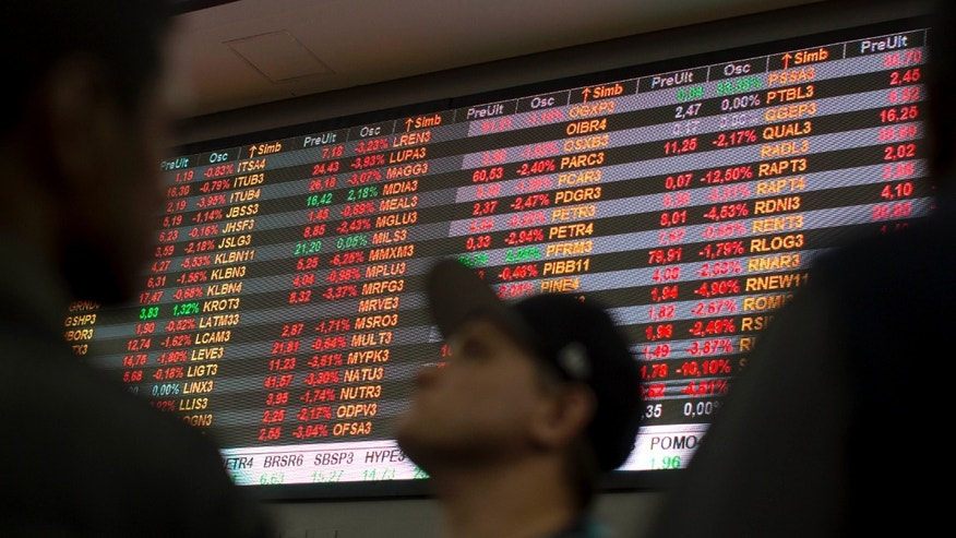 Visitors look at stock price monitors inside the BM&F BOVESPA stock exchange headquarters in Sao Paulo, Brazil, Thursday, Sept. 10, 2015. Brazil's financial markets fell Thursday in the aftermath of credit agency Standard & Poor's downgrading the country's sovereign debt to junk status. (AP Photo/Andre Penner)