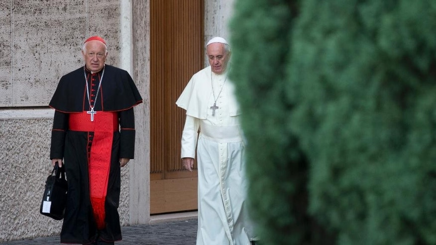 FILE - In this Oct. 9, 2014 file photo, Pope Francis, right, walks with Chile's Cardinal Ricardo Ezzati to a session of the synod, a two-week meeting of cardinals and bishops from around the world, at the Vatican. Private e-mails show that Ezzati exchanged messages with his predecessor, Cardinal Francisco Javier Errazuriz, to try to block a victim of sex-abuse by a pedophile priest from joining the papal commission. The Archbishop of Santiago de Chile has confirmed the authenticity of the e-mails. (AP Photo/Alessandra Tarantino, File)