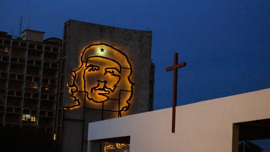 "A sculpture of revolutionary hero Ernesto ""Che"" Guevara is lit up on a government building in Revolution Square beside an altar under construction ahead of Pope Francis' Mass in Havana, Cuba, Thursday, Sept. 10, 2015. The Mass is scheduled for Sept. 20. (AP Photo/Desmond Boylan)"