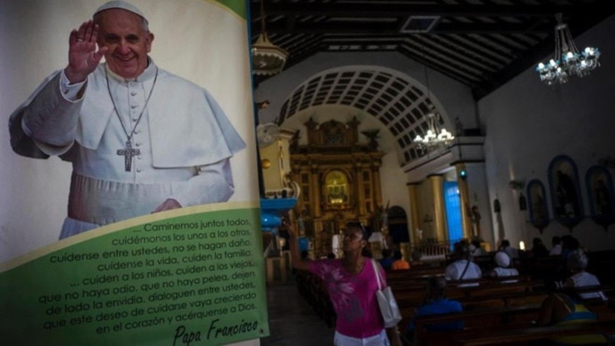 CORRECTS HOW MANY POPES HAVE VISITED CUBA - A woman prays next to a photo of Pope Francis before a procession honoring the Virgin of Regla in the town of Regla, across the bay from Havana, Cuba, Monday, Sept. 7, 2015. Pope Francis will visit Cuba on his way to the United States in September 19, making him the third Pontiff to visit the island nation. (AP Photo/Ramon Espinosa)