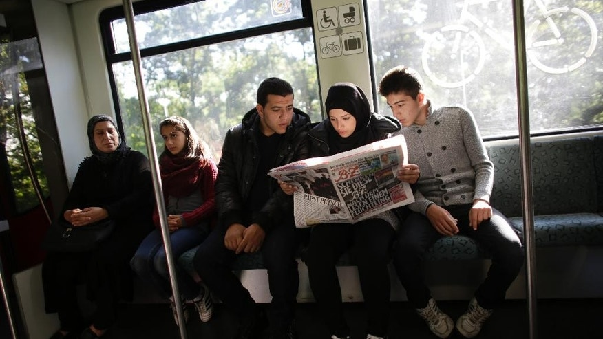 In this photo taken on Wednesday, Sept. 9, 2015, Syrian refugee family, Reem Habashieh, second from right, and her brothers Yaman Habashieh, right, and Mohammed Habashieh, center, sit in a train and read in that day's edition of the local news paper BZ with special pages in Arabic for refugees, on their way from their temporary accommodation facility to the central registration center for refugees and asylum seekers LaGeSo (Landesamt fuer Gesundheit und Soziales - State Office for Health and Social Affairs) in Berlin. Right are the mother Khawla Kreem with the youngest doughtier Raghad Habashieh. The family arrived in Berlin around a week ago, five of the 37,000 who have flooded into Germany this month seeking a new life.  (AP Photo/Markus Schreiber)