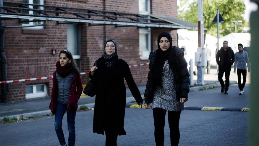 In this photo taken on Wednesday, Sept. 9, 2015, Syrian refugee family, Reem Habashieh, right, her mother Khawla Kreem, center, sister Raghad Habashieh and the brothers Yaman Habashieh, background right, and Mohammed Habashieh, back ground left, walk from their temporary accommodation facility to go to the central registration center for refugees and asylum seekers LaGeSo (Landesamt fuer Gesundheit und Soziales - State Office for Health and Social Affairs) in Berlin. The family arrived in Berlin around week ago, five of the 37,000 who have flooded into Germany this month seeking a new life. (AP Photo/Markus Schreiber)
