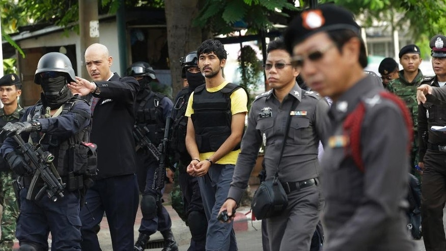 "In this Sept. 9, 2015 photo, police officers escort a key suspect in last month's Bangkok bombing, center in yellow shirt, identified by Thai police as Yusufu Mierili, traveling on a Chinese passport, but his nationality remains unconfirmed, outside Hua Lamphong railway station during a re-enactment for the Aug. 17 bombing at Bangkok's popular Erawan Shrine. In the country, the public doesn't have to settle for ""perp walks,"" where police trot high-profile suspects past the media on their way to court or jail. Authorities here make the accused go through all the motions of their alleged crimes - robberies, murders and even rapes - while the cameras roll. (AP Photo/Sakchai Lalit)"