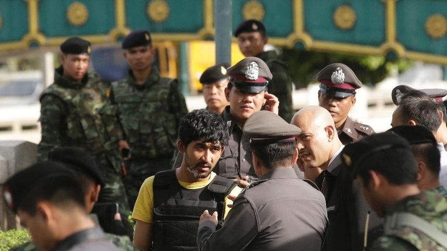 "In this Sept. 9, 2015 photo, police officers talk to a key suspect in last month's Bangkok bombing, center in yellow shirt, identified by Thai police as Yusufu Mierili, traveling on a Chinese passport, but his nationality remains unconfirmed, outside Hua Lamphong railway station during a re-enactment for the Aug. 17 bombing at Bangkok's popular Erawan Shrine. In the country, the public doesn't have to settle for ""perp walks,"" where police trot high-profile suspects past the media on their way to court or jail. Authorities here make the accused go through all the motions of their alleged crimes - robberies, murders and even rapes - while the cameras roll. (AP Photo/Sakchai Lalit)"