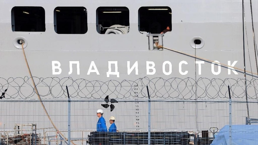 FILE - In this Sept.5, 2014 file photo, workers walk past the the Vladivostok warship on the port of Saint-Nazaire, western France. France will refund 950 million euro ($1 billion) to Russia for the cancellation of the sale of two Mistral-class warships, but avoid paying penalties. (AP Photo/David Vincent, File)