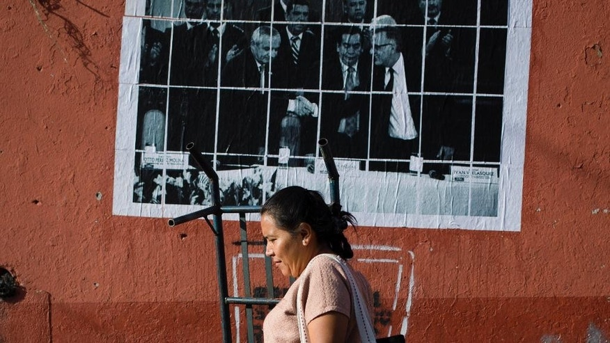 In this Aug. 27, 2015 photo, a woman walks next to an image showing Guatemala's President Otto Perez Molina shaking hands with commissioner Ivan Velasquez, of the United Nations International Commission Against Impunity, posted on a market wall in Guatemala City. Arriving in Guatemala in 2013 with a long track record of taking on the powerful in his native Colombia, Velasquez began to scrutinize the country's networks of corruption. Citizens, politicians, lawyers and journalists passed through his office, both seeking and offering information. (AP Photo/Moises Castillo)