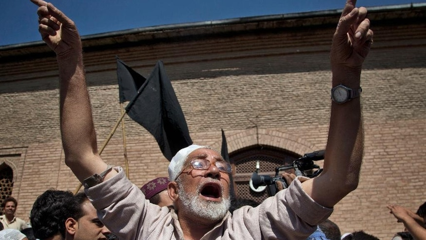 A Kashmiri Muslim protester shouts slogans during a protest in Srinagar, Indian controlled Kashmir, Friday, Sept. 11, 2015. Hundreds of Kashmiris chanted anti-government slogans and hurled stones at police protesting a court ruling upholding a colonial-era law banning cow slaughter and the sale of beef in the Indian portion of Kashmir. (AP Photo/Dar Yasin)