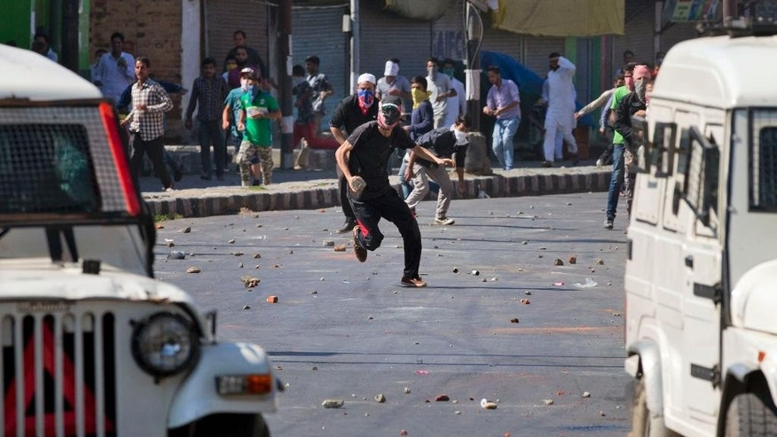 A Kashmiri Muslim protesters throws stones and bricks at Indian police vehicles during a protest in Srinagar, Indian controlled Kashmir, Friday, Sept. 11, 2015. Hundreds of Kashmiris chanted anti-government slogans and hurled stones at police protesting a court ruling upholding a colonial-era law banning cow slaughter and the sale of beef in the Indian portion of Kashmir. (AP Photo/Dar Yasin)