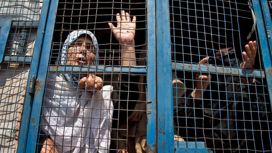 Yasmeen Raja, left, chairperson of Muslim Khawateen Markaz, or Muslim Women's Center, shouts slogans from Inside a police vehicle after she was detained along with her supporters during a protest in Srinagar, Indian controlled Kashmir, Friday, Sept. 11, 2015. Hundreds of Kashmiris chanted anti-government slogans and hurled stones at police protesting a court ruling upholding a colonial-era law banning cow slaughter and the sale of beef in the Indian portion of Kashmir. (AP Photo/Dar Yasin)