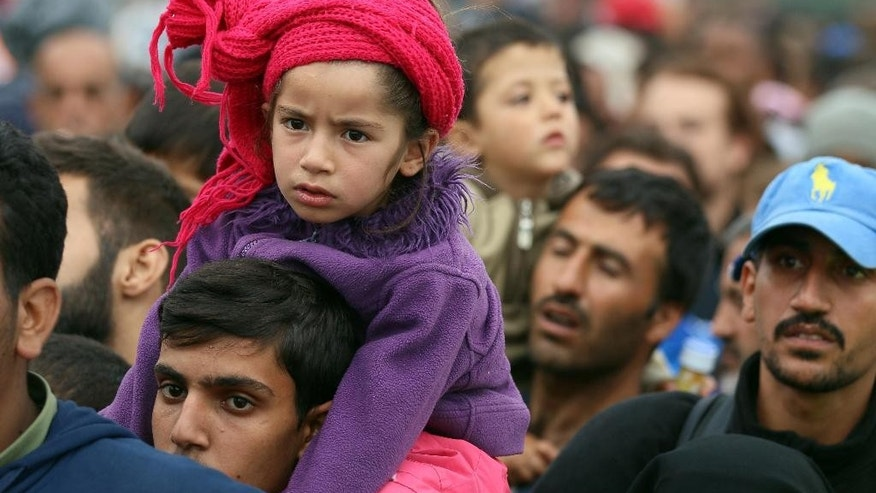 A girl sits on the shoulders of a man as migrants wait to board busses after crossing the Hungarian-Austrian border in Nickelsdorf, 70 kilometers (43 miles) southeast of Vienna, Friday, Sept. 11, 2015. (AP Photo/Ronald Zak)