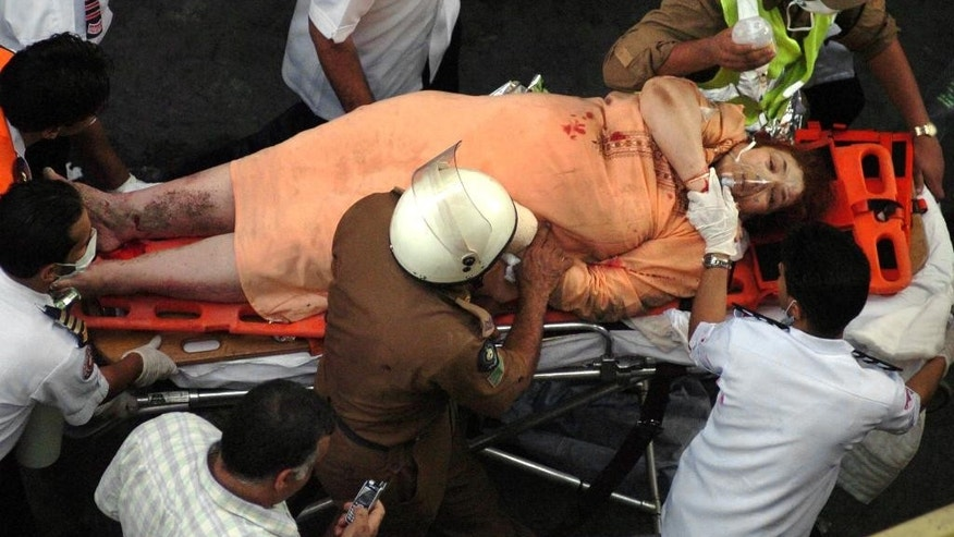 FILE - In this Jan. 5, 2006 file photo, an injured woman is taken away by rescuers at the scene of a building collapse in Mecca, Saudi Arabia. The day before the hajj began, an eight-story building being used as a hostel near the Grand Mosque in Mecca collapsed, killing at least 73 people and injuring 62.(AP Photo, File)