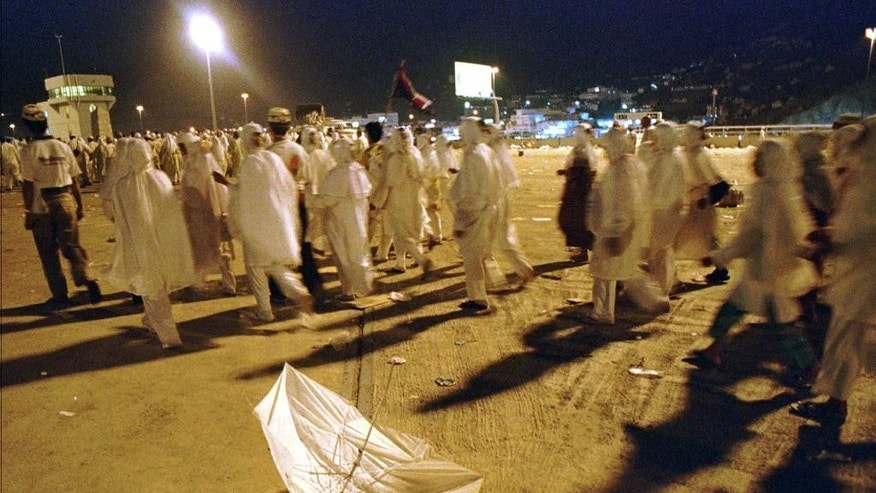 "FILE - In this April 9, 1998 file photo, pilgrims walk past a broken umbrella left on the ground at the site of a stampede at Mina, Saudi Arabia. The stampede broke out as Muslims rushed to perform a religious duty known as ""stoning the devil"", where supplicants hurl stones at pillars symbolizing the temptations of Satan. (AP Photo/Kamran Jebreili, File)"