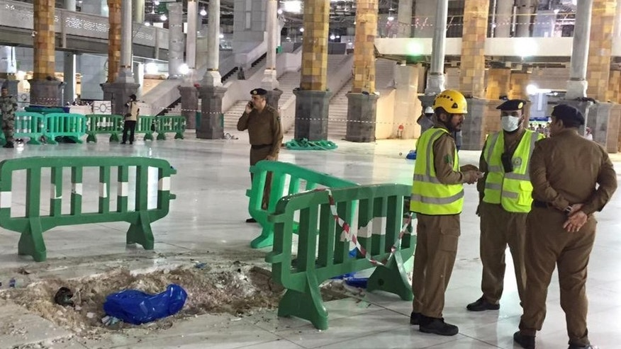 In this image released by the Saudi Interior Ministry's General Directorate of Civil Defense, Civil Defense officials inspect the damage at the Grand Mosque in Mecca after a crane collapsed killing dozens, Friday, Sept. 11, 2015. The accident happened as pilgrims from around the world converged on the city, Islam's holiest site, for the annual Hajj pilgrimage, which takes place this month. (Saudi Interior Ministry General Directorate of Civil Defense via AP)