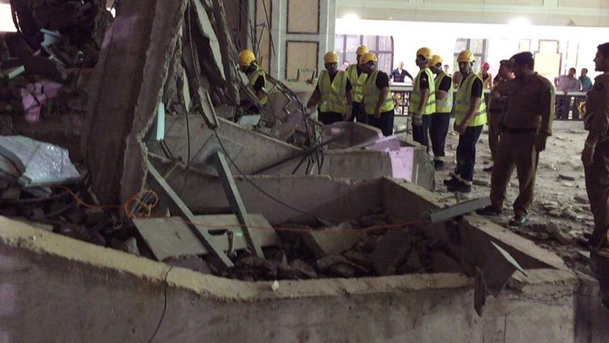 In this image released by the Saudi Interior Ministry's General Directorate of Civil Defense, Civil Defense personnel inspect the damage at the Grand Mosque in Mecca after a crane collapsed killing dozens, Friday, Sept. 11, 2015. The accident happened as pilgrims from around the world converged on the city, Islam's holiest site, for the annual Hajj pilgrimage, which takes place this month. (Saudi Interior Ministry General Directorate of Civil Defense via AP)