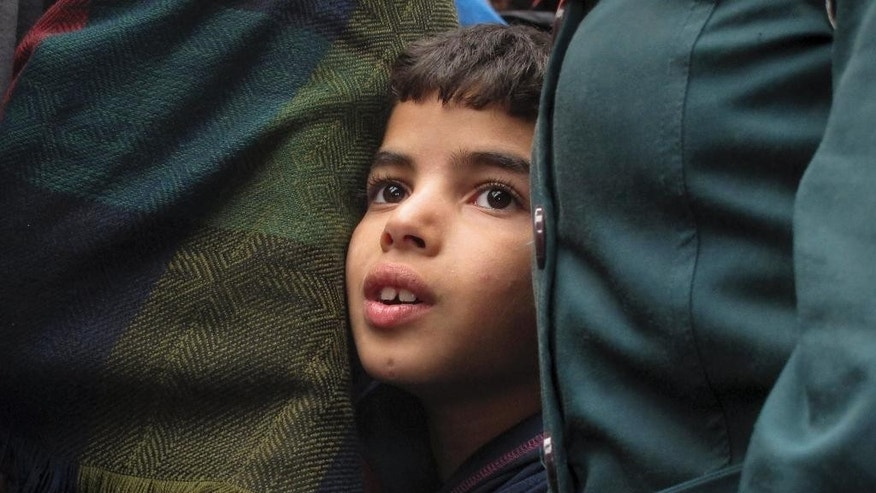 A young boy looks into the camera besides a group of migrants after crossing the Serbian-Hungarian border near Roszke, southern Hungary, Friday, Sept. 11, 2015. EU officials and human rights groups say they've been disappointed by the animosity toward asylum-seekers in countries from which hundreds of thousands of people fled communist dictatorships just decades ago. (AP Photo/Matthias Schrader)