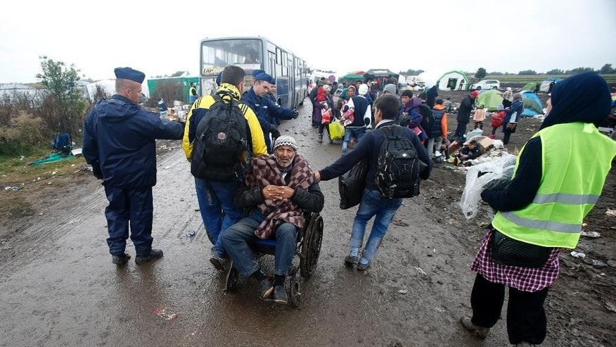Migrants pull the wheelchair of disabled man in front of a makeshift camp for asylum seekers near Roszke, southern Hungary, Friday, Sept. 11, 2015. EU officials and human rights groups say they've been disappointed by the animosity toward asylum-seekers in countries from which hundreds of thousands of people fled communist dictatorships just decades ago. (AP Photo/Darko Vojinovic)