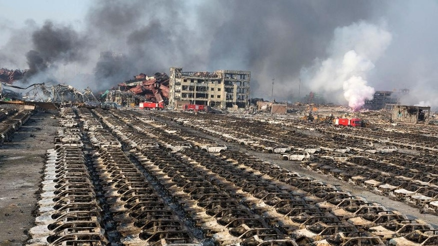 FILE - In this Aug. 13, 2015, file photo, smoke billows from the site of an explosion that reduced a parking lot filled with new cars to charred remains at a warehouse in northeastern China's Tianjin municipality. Chinese authorities said on Saturday, Sept. 12, that they've ended the search for the remaining missing in a massive chemical warehouse explosion last month, setting the final death toll at 173 in China's worst industrial disaster in years. (AP Photo/Ng Han Guan, File)