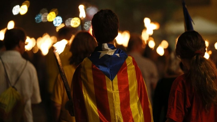 People burn torches during a march for the independence of Catalonia in Barcelona, Spain, Thursday, Sept. 10, 2015. For a fourth consecutive year, hundreds of thousands of pro-independence Catalans are expected to rally Friday to break away from Spain, kicking off a fresh secession bid in a push to carve out a new European nation. (AP Photo/Manu Fernandez)