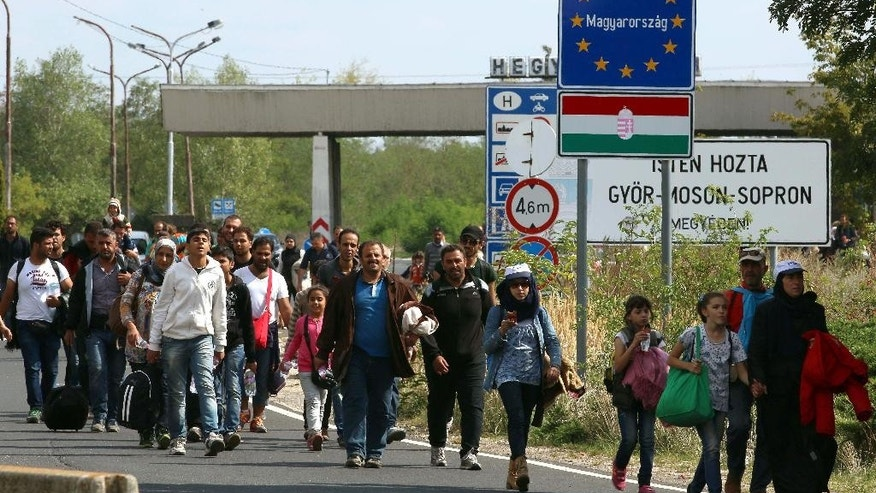 Migrants and refugees cross  the border between Hungary and Austria, near Nickelsdorf, Austria,  Thursday, Sept. 10, 2015. Austrian police say more than 3,000 migrants crossed into Austria overnight at Nickelsdorf, the main border point with Hungary. (AP Photo/Ronald Zak)