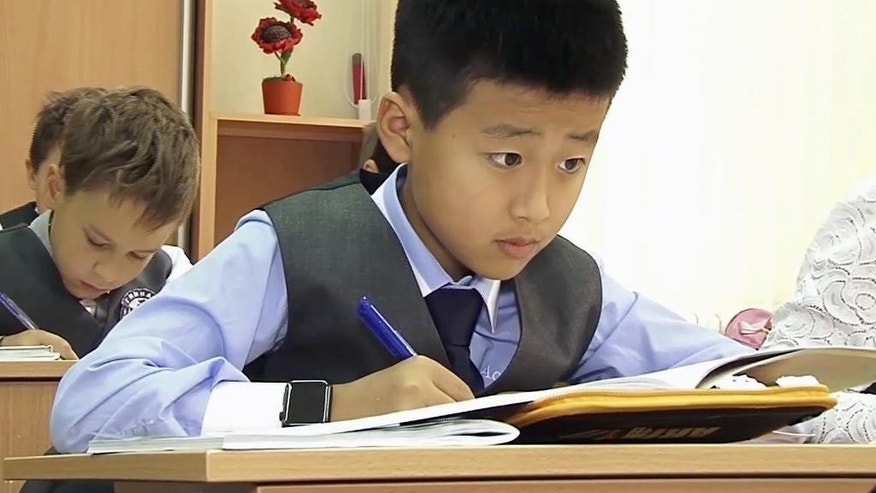 In this image made from video taken Wednesday, Sept. 9, 2015, fourth-grade students from Russia and North Korea study together in a classroom at a school in Khabarovsk, Russia's Far East. The class, with seven students from North Korea, is taking part in a new program in the city of Khabarovsk that aims to promote cultural understanding between the neighboring countries. (AP Photo)
