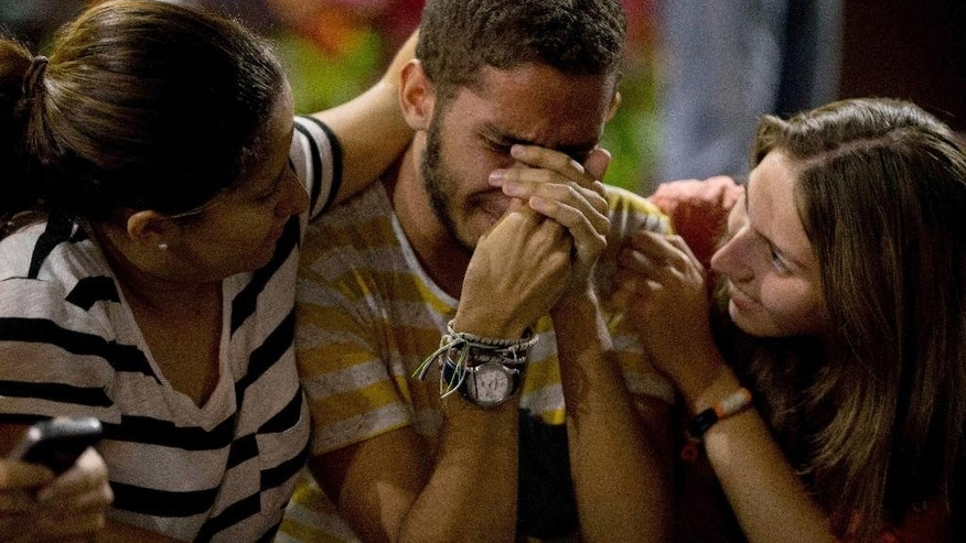 Supporters of opposition leader Leopoldo Lopez cry as they listen to Lopez's guilty verdict in Caracas, Venezuela, Thursday, Sept. 10, 2015. Lopez has been found guilty of inciting violence for his role as leader of a sometimes bloody protest movement in 2014, and was sentenced to almost 14 years in prison. (AP Photo/Fernando Llano)