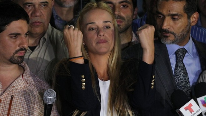 Lilian Tintori, wife of jailed opposition leader Leopoldo Lopez, center, gestures during a news conference at Bolivar square in Chacao municipality, in Caracas, Venezuela, Thursday, Sept. 10, 2015. Lopez has been found guilty of inciting violence for his role as leader of a sometimes bloody protest movement in 2014, and was sentenced to almost 14 years in prison. (AP Photo/Fernando Llano)