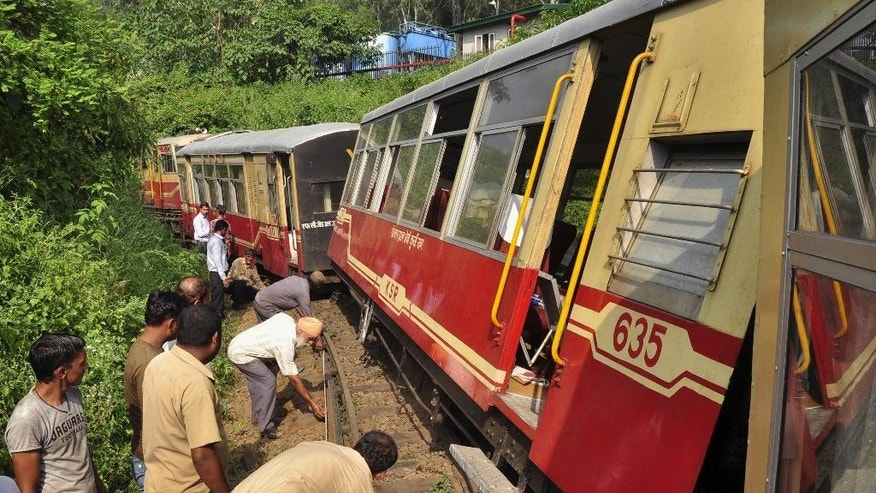 Indian police and volunteers inspect the site of a train derailment in Himachal Pradesh state, India, Saturday, Sept. 12, 2015. Three coaches of a special tourist train went off the tracks near the northern hill town of Kalka on Saturday, killing two British women tourists. (AP Photo/Kapil Sethi)
