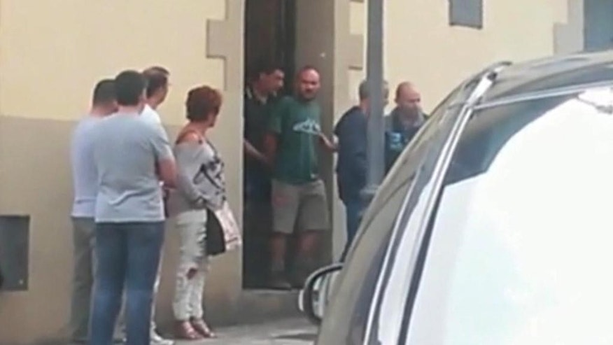 "In this image from TV taken on Friday Sept. 11, 2015 and made available Saturday Sept. 12, 2015, authorities lead suspect Miguel Angel Munoz, center in green, out of a building, in Grandas de Salime, northwest Spain. A body found on a rural property in northwest Spain is most likely that of an American woman who went missing while walking along a pilgrimage route, officials said Saturday. Interior Minister Jorge Fernandez Diaz said evidence pointed to the remains being those of Denise Thiem and there were ""well-founded suspicions"" that the 39-year-old prime suspect arrested over her disappearance was responsible for her death. (Rocio Ferreira via APTN)"