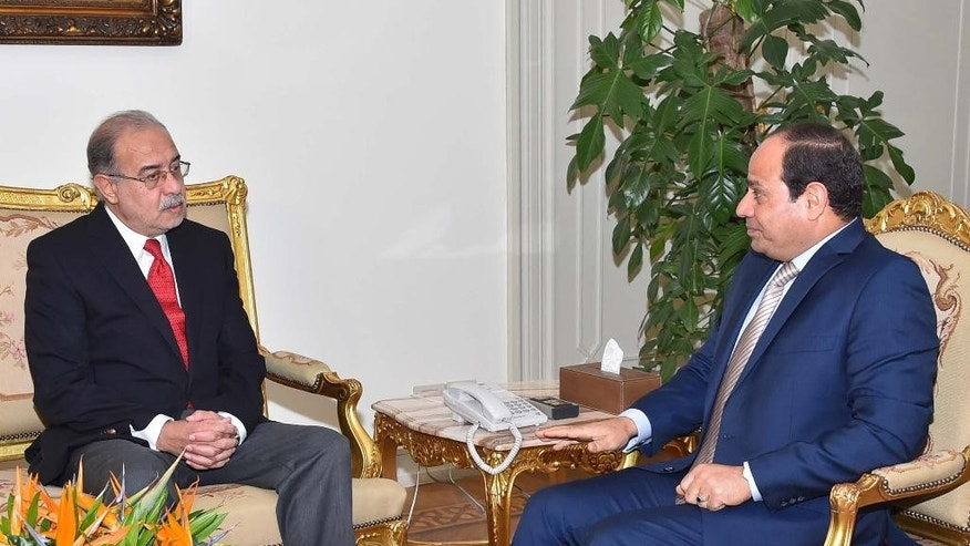 In this photo provided by Egypt's state news agency MENA, Egyptian President Abdel-Fattah el-Sissi, right, meets with Petroleum Minister Sheriff Ismail in Cairo, Egypt, Saturday, Sept. 12, 2015. Prime Minister Ibrahim Mehleb and his Cabinet resigned Saturday in the face of intense criticism from state-friendly media that reflects growing discontent but stops short of faulting el-Sissi, the former general who led the overthrow of an Islamist president two years ago. El-Sissi tasked Ismail with forming a new Cabinet within a week. (MENA via AP)