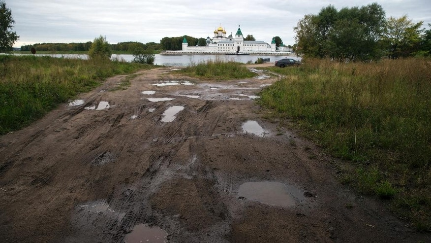In this photo taken Thursday, Sept. 10, 2015 a dirt path leads to the Volga River with the Ipatievsky Monastery in the background in Kostroma, 350 km (218 miles) northeast of Moscow, Russia. Voters will go to polls on Sunday across Russia, and the anti-Putin opposition was allowed to run in only one Russian region, Kostroma. (AP Photo/Pavel Golovkin)
