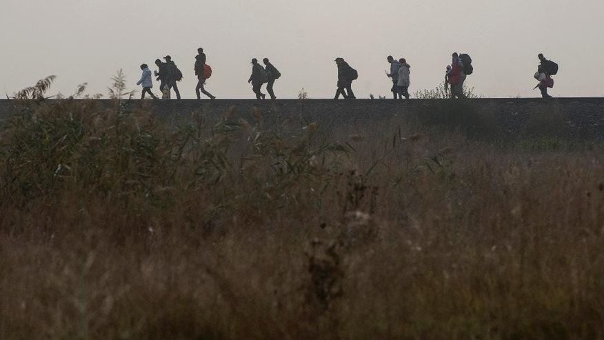 People walk on the railway track after crossing the border line between Serbia and Hungary in Roszke, southern Hungary, Saturday, Sept. 12, 2015. Hundreds of thousands of Syrian refugees and others are still making their way slowly across Europe, seeking shelter where they can, taking a bus or a train where one is available, walking where it isn't. The latest string of walkers made their way Friday from the Hungarian border across Austria toward the capital, Vienna. (AP Photo/Christian Bruna)