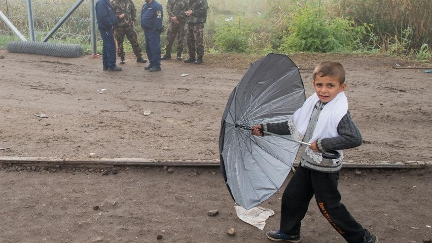 A young boy walks with his umbrella besides Hungarian soldiers and police officers at the border line between Serbia and Hungary in Roszke, southern Hungary, Saturday, Sept. 12, 2015. Hundreds of thousands of Syrian refugees and others are still making their way slowly across Europe, seeking shelter where they can, taking a bus or a train where one is available, walking where it isn't. The latest string of walkers made their way Friday from the Hungarian border across Austria toward the capital, Vienna. (AP Photo/Christian Bruna)