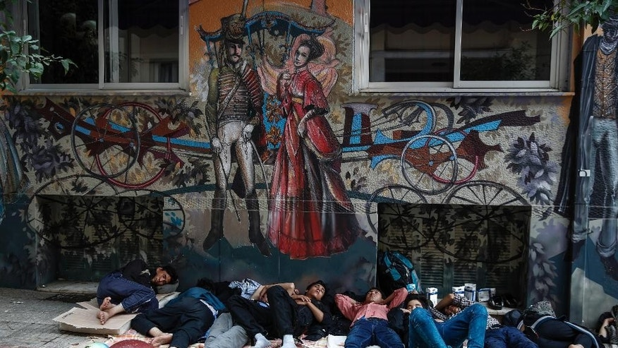 People sleep outside a building near Victoria Square, Athens, where hundreds of migrants and refugees have temporarily camped, on Saturday, Sept. 12, 2015. The European Union will assess the economic costs of the refugee crisis to see whether the nations caught up in it need more lenient budget rules. Greece, Italy and Hungary are among the EU nations hardest hit by the arrival of tens of thousands of migrants this year. (AP Photo/Yorgos Karahalis)