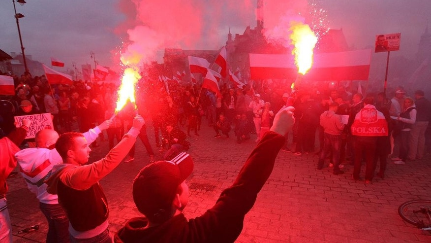 Several thousand right wing nationalists wave Polish national flags and burn flares as they march through the downtown, demonstrating against EU proposed quotas for Poland to spread the human tide of refugees around the Europe, in Warsaw, Poland, Saturday, Sept. 12, 2015. (AP Photo/Czarek Sokolowski)