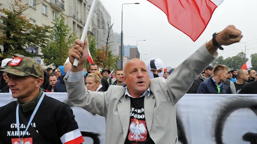 Protesters shout anti migrant slogans as several thousand right wing nationalists march through downtown, demonstrating against EU proposed quotas for Poland to spread the human tide of refugees around Europe, in Warsaw, Poland, Saturday, Sept. 12, 2015. (AP Photo/Alik Keplicz)