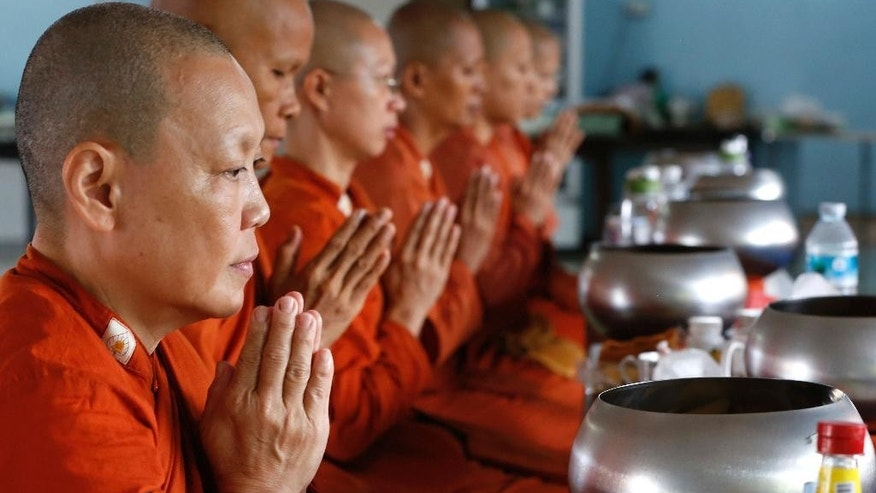 In this Aug. 23, 2015, photo, women Buddhist monks pray at the Songdhammakalyani Monastery in Nakhon Pathom, Thailand. The top Buddhist authority in Thailand bars women from becoming monks. Thailand has some 100 bhikkhunis who were ordained in Sri Lanka, where women are allowed to become monks. They and their monasteries are not legally recognized in Thailand, and don't enjoy state funding and other support the country's 200,000 male monks are granted. (AP Photo/Penny Yi Wang)