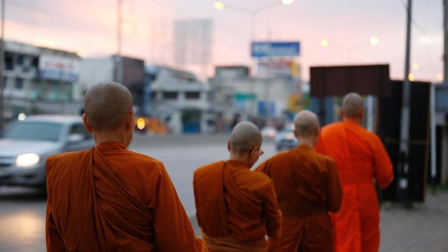 In this Aug. 23, 2015, photo, women Buddhist monks walk during their morning alms rounds in Nakhon Pathom, Thailand. The top Buddhist authority in Thailand bars women from becoming monks. Thailand has some 100 bhikkhunis who were ordained in Sri Lanka, where women are allowed to become monks. They and their monasteries are not legally recognized in Thailand, and don't enjoy state funding and other support the country's 200,000 male monks are granted. (AP Photo/Penny Yi Wang)