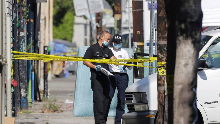 Los Angeles Police Department investigators work at a crime scene, where three children have been found dead inside a car parked outside an elementary school while a man found with them is in critical condition in South Los Angeles Wednesday, Sept. 9, 2015. Officer Jack Richter says the three children were declared dead at the scene while a man found with them was taken to a nearby hospital, also with stab wounds. His relationship to the children wasn't immediately clear. (AP Photo/Nick Ut)