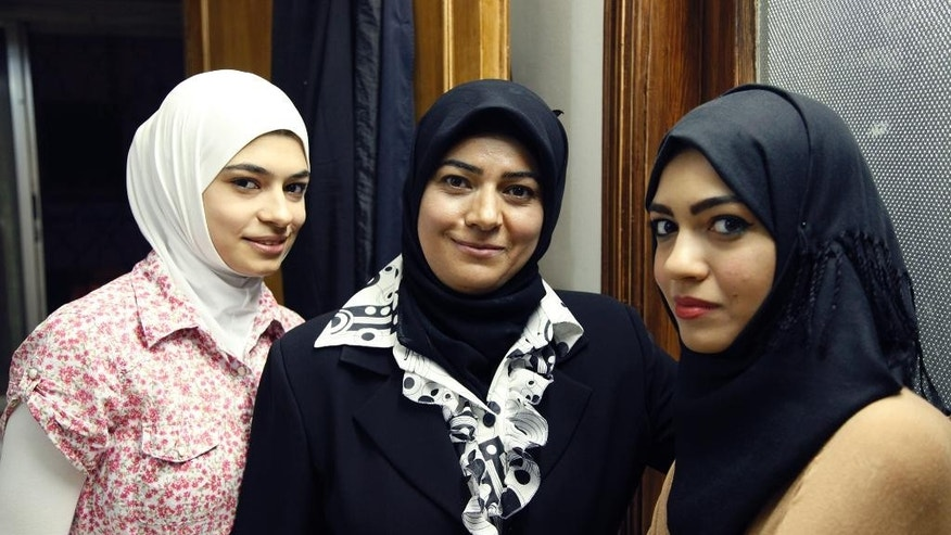 ?In this Thursday, Sept. 10, 2015 photo, Amena Abomosa, 43, center, poses for a photo with her daughters Isra,18, left, and Reemaz, 17, at their family home in Amman, Jordan. The family fled Damascus, Syria for Jordan after Abomosa's husband was killed by a sniper while trying to save a wounded child. A single mother with three kids supporting a grandmother with cancer, Abomosa is headed to France on Monday, Sept. 14, 2015, a rare recipient of legal migration papers. (AP Photo/Sam McNeil)