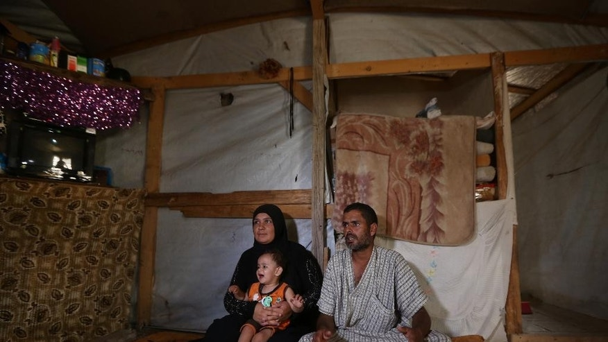 In this Thursday, Sept. 10, 2015, Syrian refugee Ghazi Helal, 28, right, speaks during an interview with The Associated Press as his wife Rim, 25, and 17-month-old son Mohammed sit next to him inside their tent at a Syrian refugee camp in the town of Deir Zanoun, Bekaa Valley, Lebanon. The Helal family is willing to risk the arduous, dangerous journey to Europe, but, among the poorest of the Syrian refugees across the region, the family can't afford to pay a smuggler. (AP Photo/Bilal Hussein)
