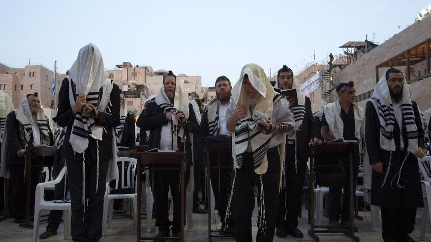 Men pray ahead of the Jewish New Year at the Western Wall, the holiest site where Jews can pray, in Jerusalem's old city, Sunday, Sep. 13, 2015. Israeli police briefly clashed with Palestinian protesters at Jerusalem's most sensitive holy site early Sunday, raising tensions in the holy city ahead of the Jewish New Year.(AP Photo/Tsafrir Abayov)