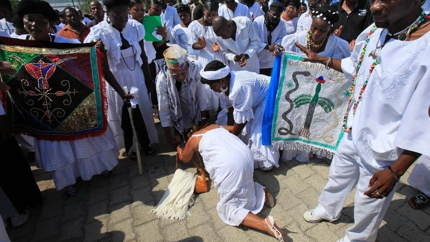 FILE - In this March 28, 2010 file photo, a woman kisses the feet of Voodoo leader Max Beauvoir during ceremony in honor of the victims of the earthquake in Port-au-Prince. A government statement said Beauvoir died Saturday, Sept. 12, 2015, in Haiti's capital, Port-au-Prince, after an illness. The cause of death was not immediately known. (AP Photo/Jorge Saenz,File)