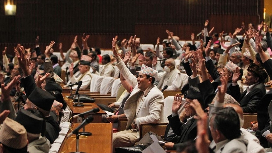 Nepalese lawmakers raise their hands as they begin voting on a draft of the new constitution at the Constituent Assembly Hall in Kathmandu, Nepal, Sunday, Sept. 13, 2015. The Himalayan nation's constitution has been delayed by years of disagreements between the main political parties, and the voting on the draft is seen as major progress. (AP Photo/Niranjan Shrestha)