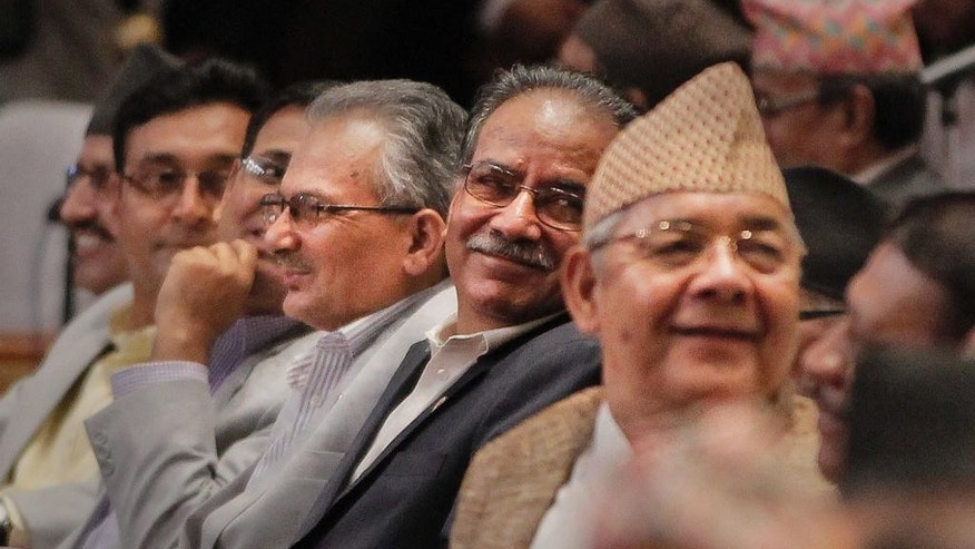 Communist Party of Nepal (Maoist) Chairman Pushpa Kamal Dahal, center, smiles as Nepalese lawmakers begin voting on a draft of the new constitution at the Constituent Assembly Hall in Kathmandu, Nepal, Sunday, Sept. 13, 2015. The Himalayan nation's constitution has been delayed by years of disagreements between the main political parties, and the voting on the draft is seen as major progress. (AP Photo/Niranjan Shrestha)