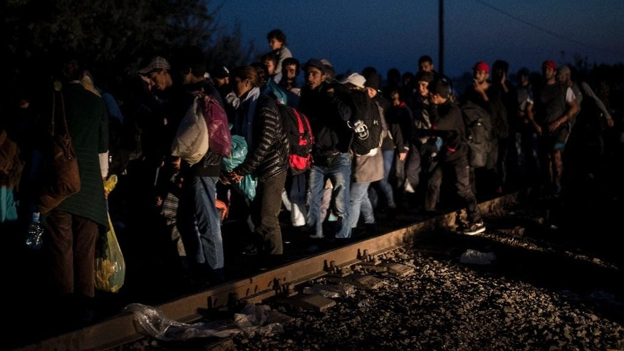 People gather at the border, near Roszke, southern Hungary , Saturday, Sept. 12, 2015. Hundreds of thousands of Syrian refugees and others are still making their way slowly across Europe, seeking shelter where they can, taking a bus or a train where one is available, walking where it isn't. (AP Photo/Christian Bruna)