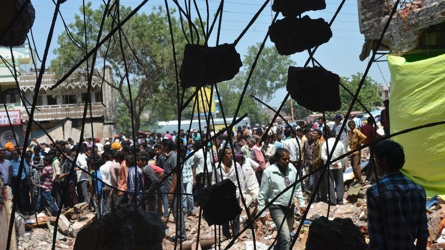 Onlookers and people looking for their missing relatives gather at the site of Saturday's explosion in the town of Petlawad in central Madhya Pradesh state, India, Sunday, Sept. 13, 2015. Police in central India on Sunday were looking for a man who was being blamed for a massive explosion at a restaurant that killed dozens, as angry residents protested the way the authorities were handling the case. (AP Photo/Ritesh Trivedi)