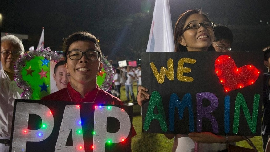 In this photo taken Friday, Sept. 11, 2015, supporters of Prime Minister Lee Hsien Loong's People's Action Party (PAP) at an assembly center in Singapore. Every four or five years Singaporeans vote in general elections without ever asking the question which party can best run the government. That's a no-brainer: It's the same party that's been ruling the wealthy Southeast Asian city-state for half-century. (AP Photo/Ng Han Guan)