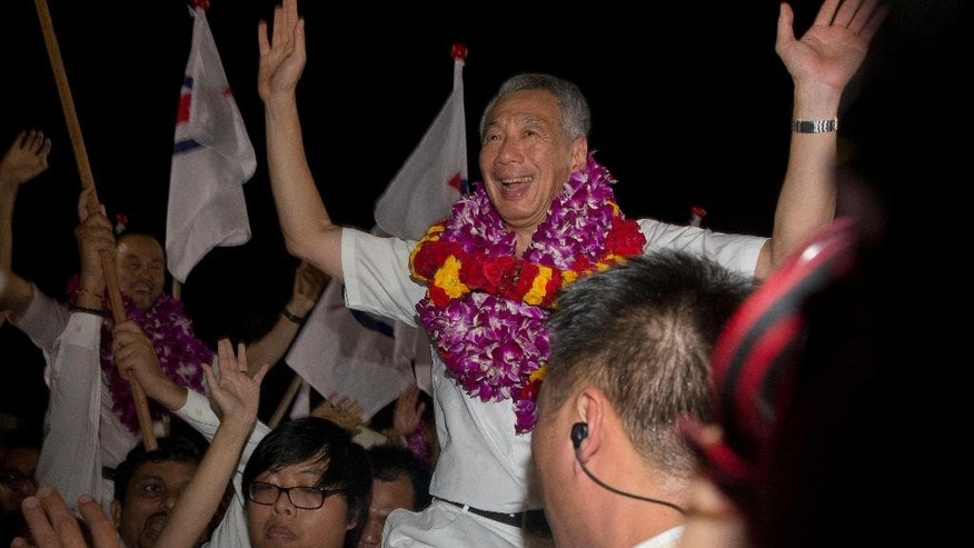 In this photo taken Saturday, Sept. 12, 2015, Singapore's Prime Minister Lee Hsien Loong of the ruling People's Action Party (PAP) celebrates a win in his constituency in Singapore. Every four or five years Singaporeans vote in general elections without ever asking the question which party can best run the government. That's a no-brainer: It's the same party that's been ruling the wealthy Southeast Asian city-state for half-century. (AP Photo/Ng Han Guan)