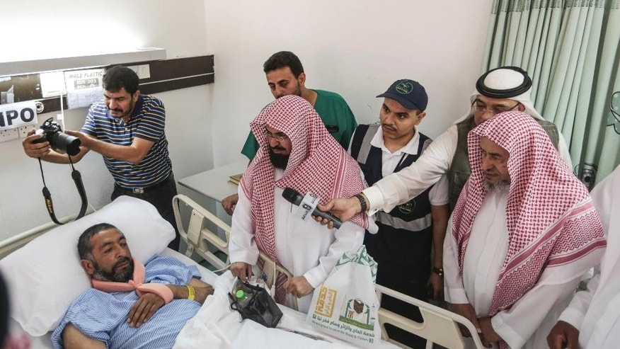 Abdul Rahman Al Sudais, Imam of the Grand Mosque in Mecca, visits one of the victims of the crane accident at the mosque at Al Nour specialist hospital in Mecca, Saudi Arabia, Sunday, Sept. 13, 2015. High winds were to blame for the toppling of a massive crane that smashed into the mosque and killed over 100 people ahead of the start of the annual hajj pilgrimage, the head of Saudi Arabia's civil defense directorate said Saturday. (AP Photo/Mosa'ab Elshamy)